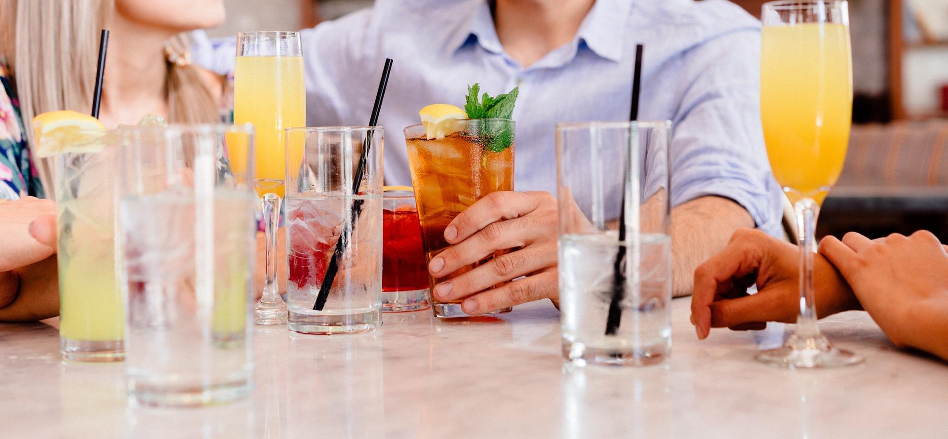 leżące na stole szklanki i napoje